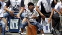 A boy playing the cajon