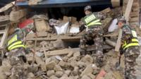 Police search ruins after a 7.9-magnitude earthquake hit Nepal