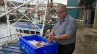 John McAlister opening a fresh scallop