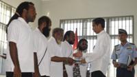 Joko Widodo shakes hands with pardoned political prisoners