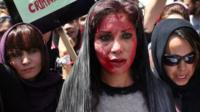 Afghan protestors, one with fake blood smeared on her face, demand justice for woman beaten to death by a mob, in Kabul, Afghanistan, 27 April 2015