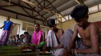 Bangladeshi migrants eating a meal in a camp for migrants in Indonesia