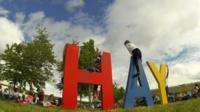 Hay letters with children playing in a field