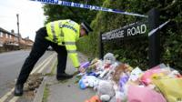 Police officer and floral tributes near murder scene