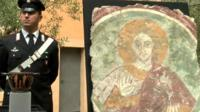 Italian police officer standing next to recovered fresco