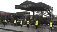 """Policemen stand guard as rescuers work on the site of a petrol station fire in Ghana""""s capital, Accra,"""