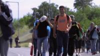 Long line of migrants walking along a road in Europe