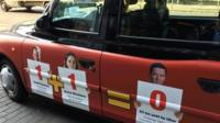 A cab with a poster depicting Uber's relationship with government