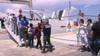 Migrants arriving in Italy from a coastguard ship