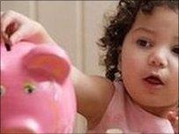 Child putting money in piggy bank