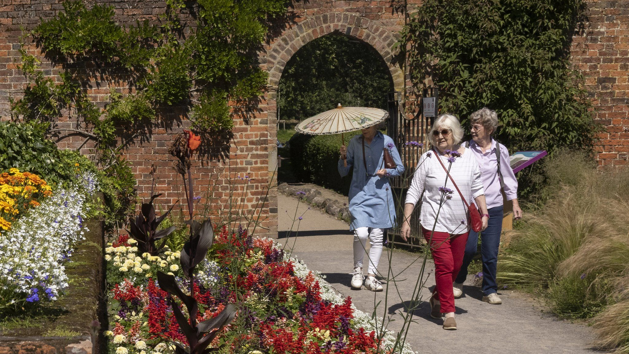 An elderly group walk along the herbaceous border in the gardens at Beckenham Place Park