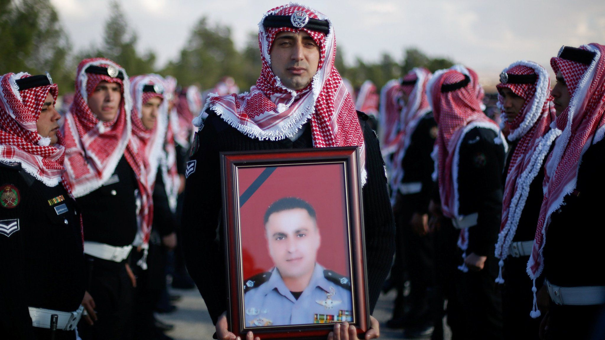 Guard of honour carries a picture of soldier killed during an attack in Karak, Jordan (19 December 2016)