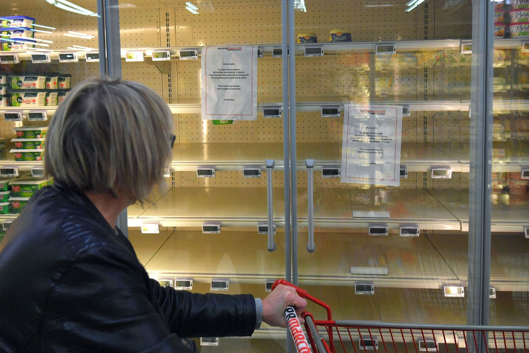 A woman reads a sign that reads, 'Due to a shortage of the raw material to make butter, we are not able to supply and sell you this product' attached to an empty refrigerated supermarket shelf on October 25, 2017 in Reze, western France.