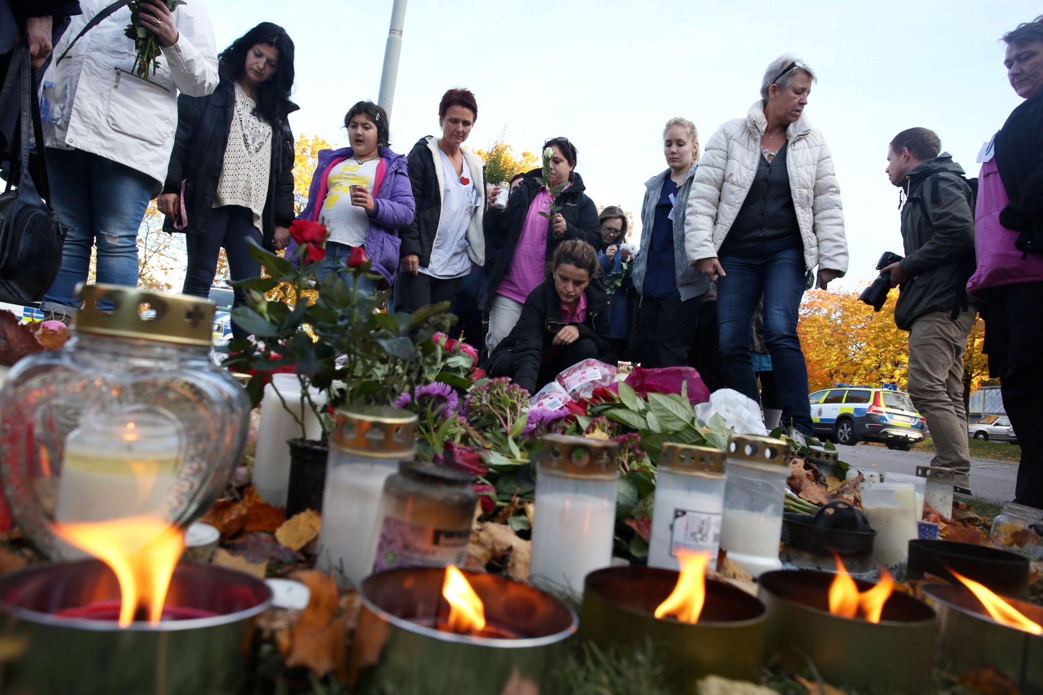 People light candles outside Kronan school in Trollhattan, Sweden, Friday Oct. 23, 2015, following a knife attack on Thursday