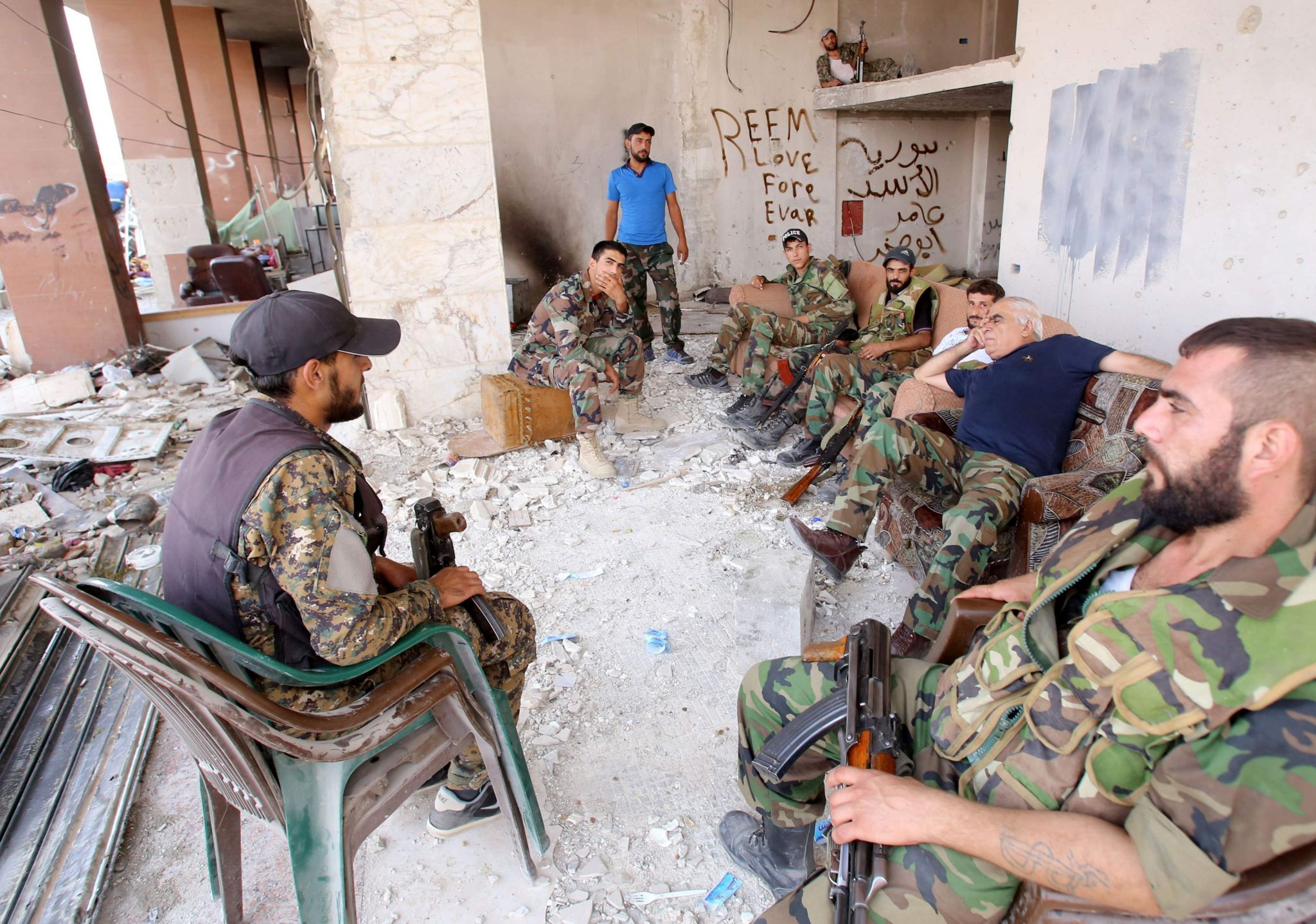 Syrian army soldiers gather at the entrance of a damaged building in the government-controlled part of the besieged town of Darayya, 26 August 2016