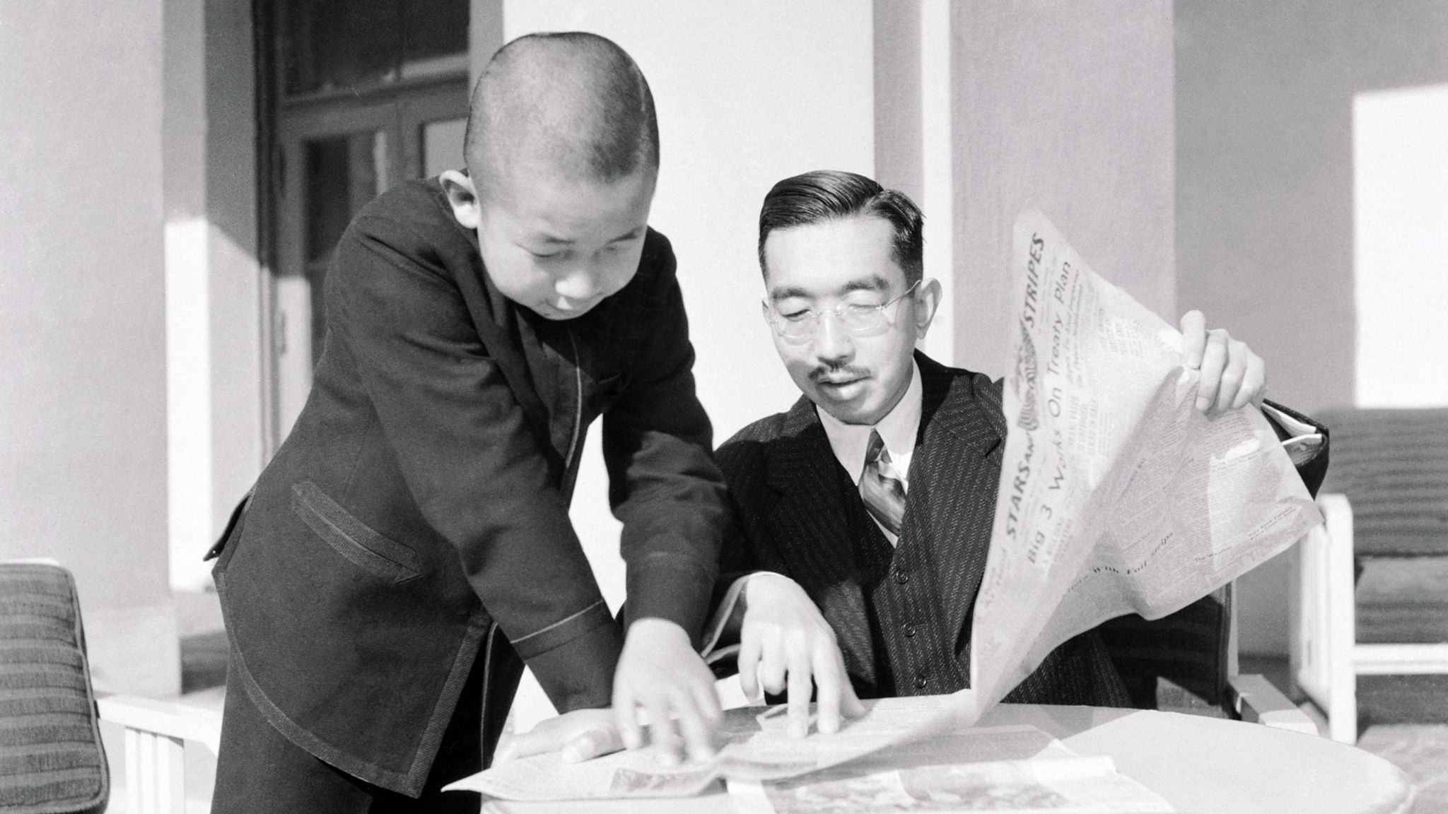 Emperor Hirohito and Prince Akihito reading a newspaper