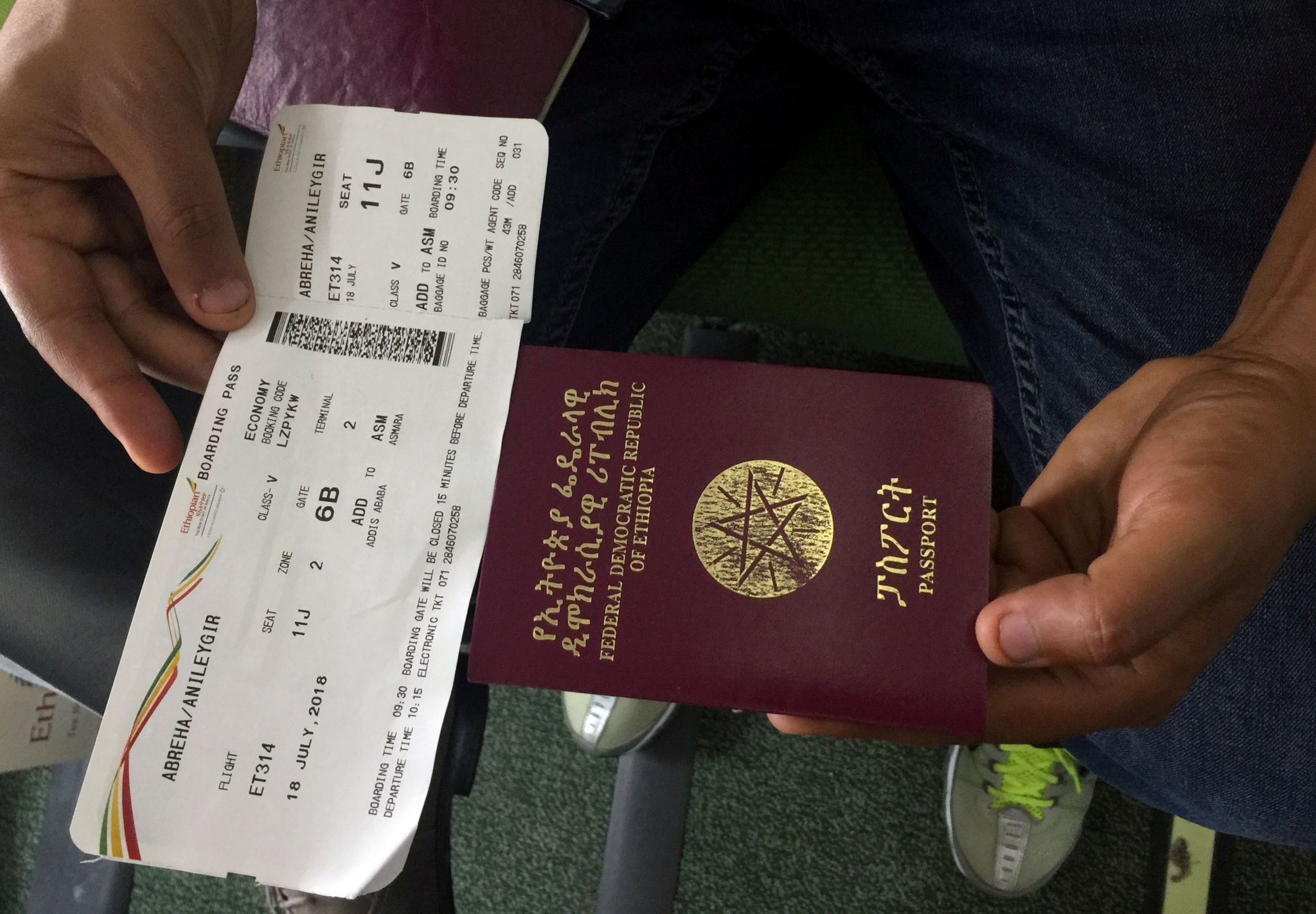 """A passenger displays an Ethiopian passport and an Ethiopian Airlines boarding pass as he sits inside ET314 flight to Eritrea""""s capital Asmara at the Bole International Airport in Addis Ababa, Ethiopia July 18, 2018."""