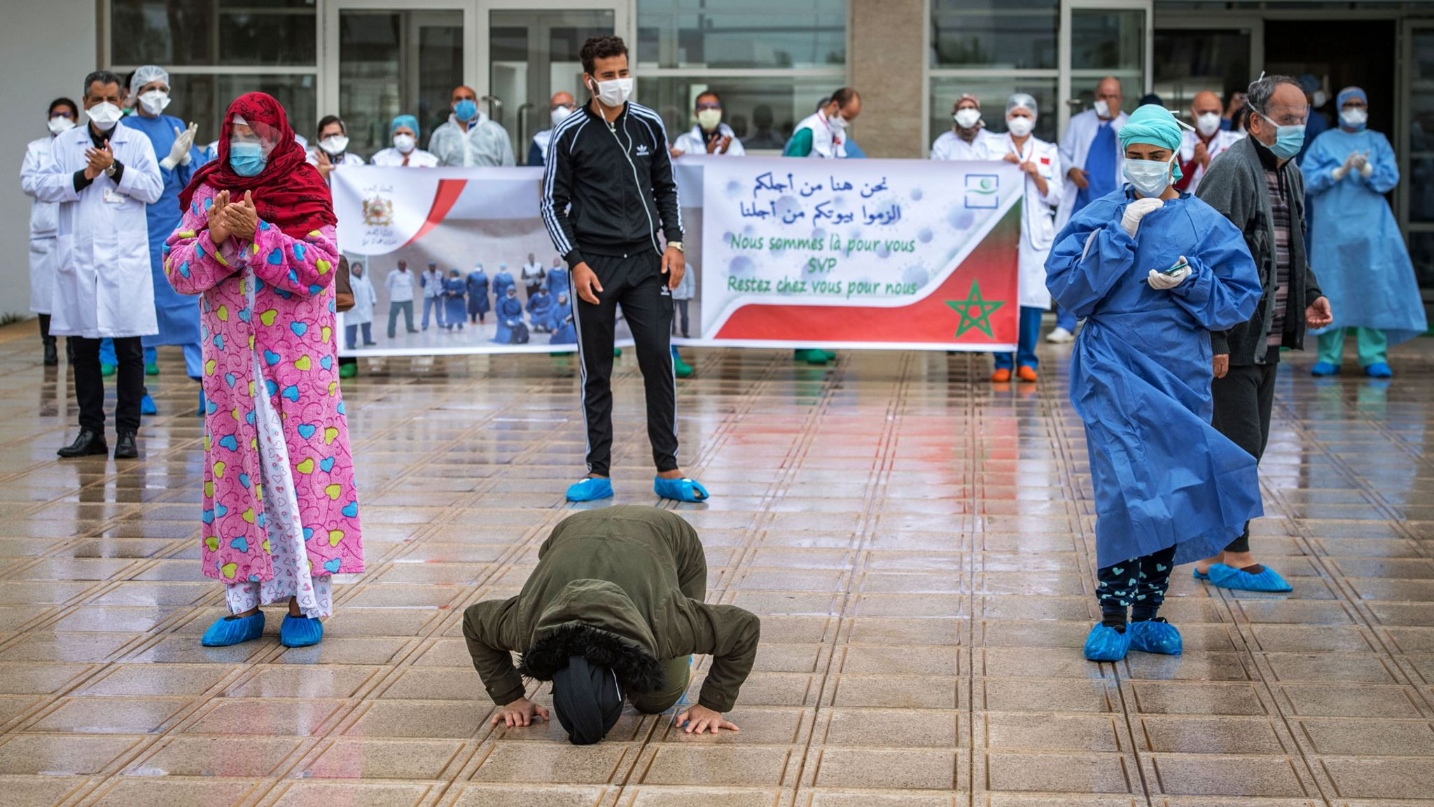 A patient who recovered from Covid-19 kisses the ground leaving hospital in the city of Sale, Morocco
