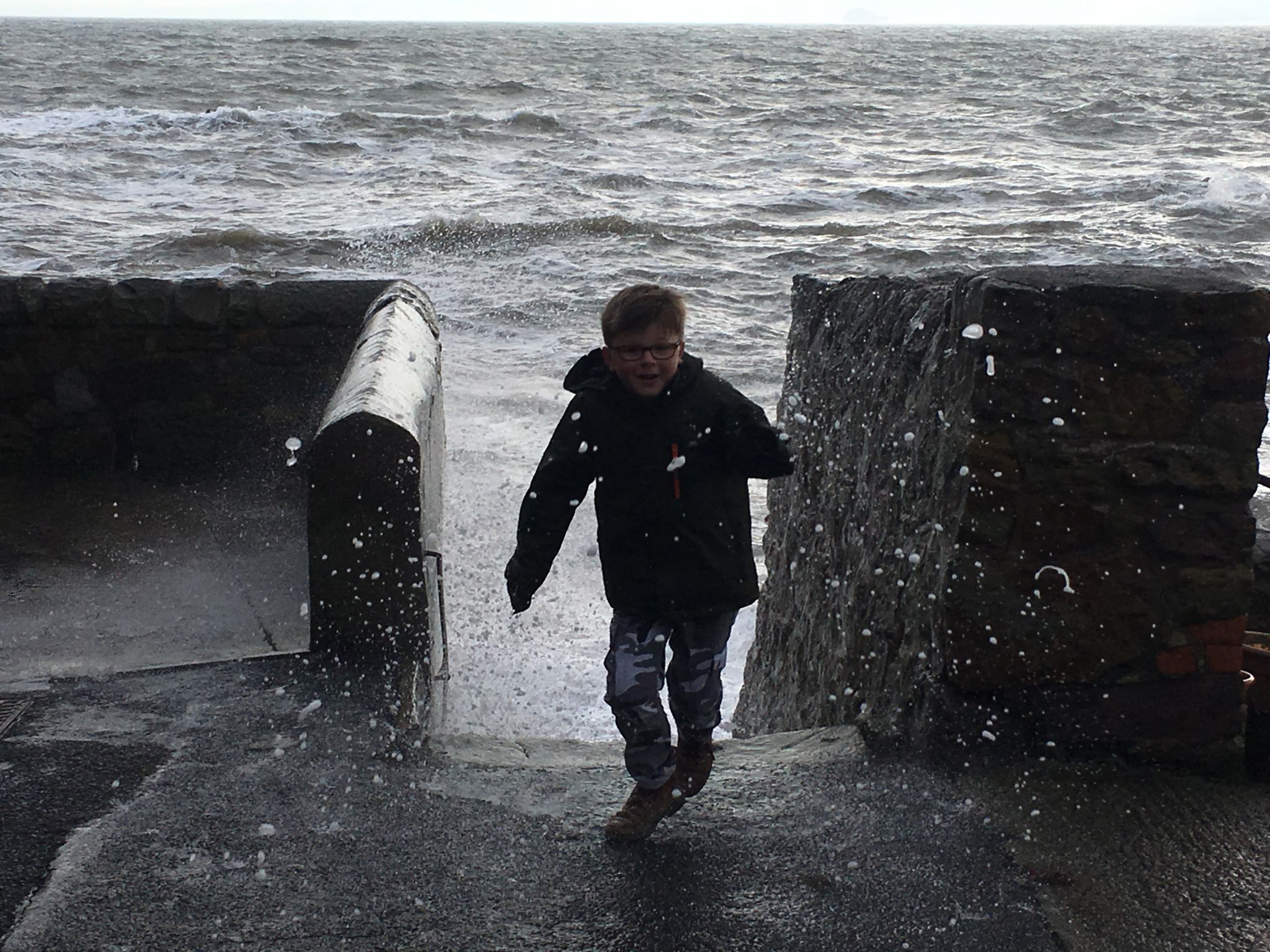 Boy running away from waves