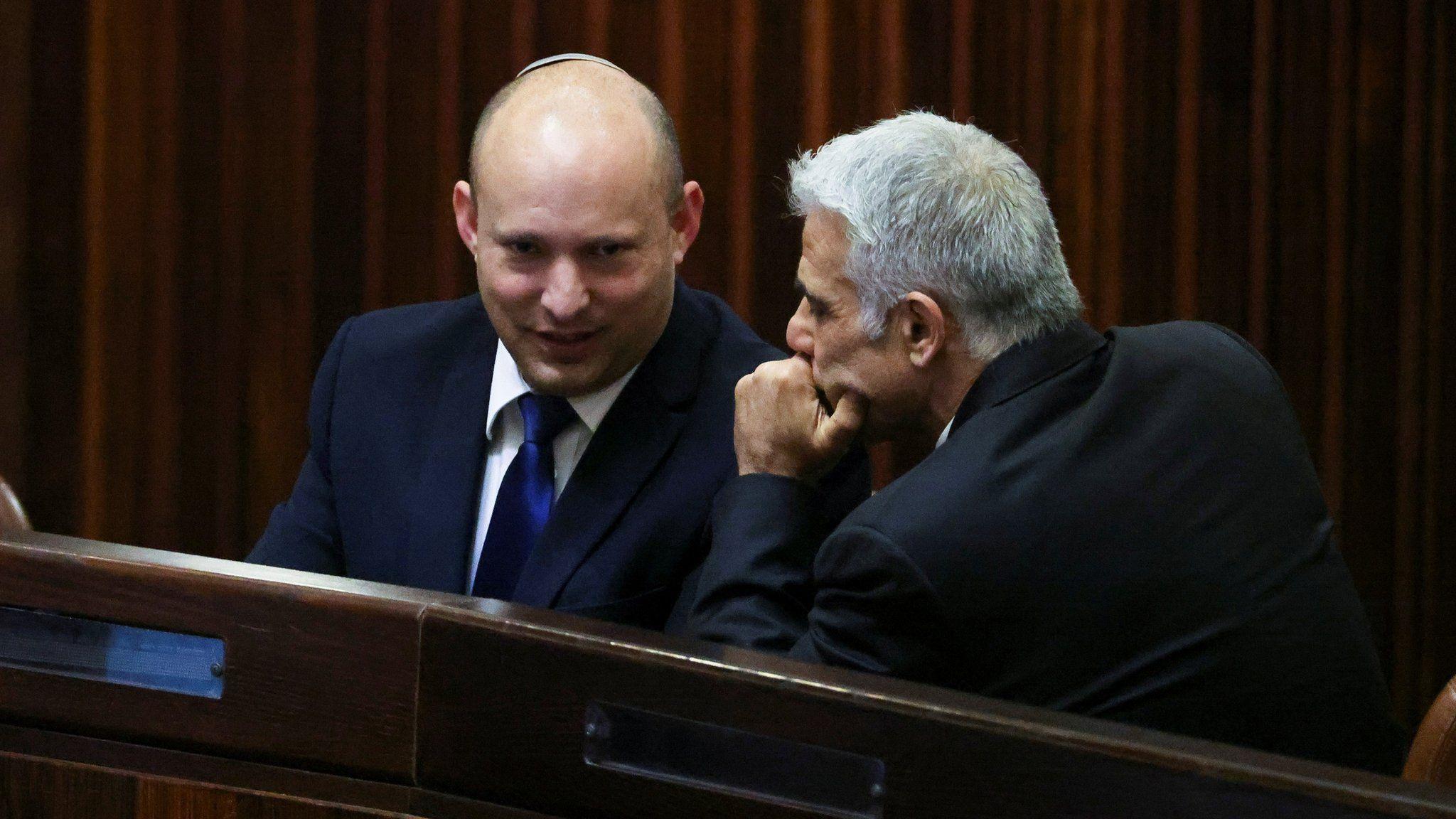 Israeli politicians Naftali Bennett (L) and Yair Lapid (R) talk during a parliamentary session in Jerusalem (2 June 2021)