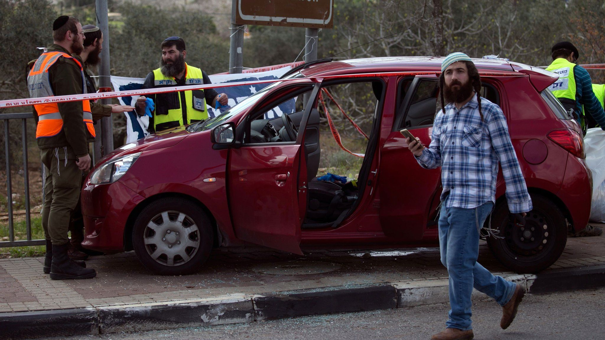 Israeli forensic specialists inspect a a car at the site of a deadly attack near the Jewish settlement of Ariel in the occupied West Bank (17 March 2019)