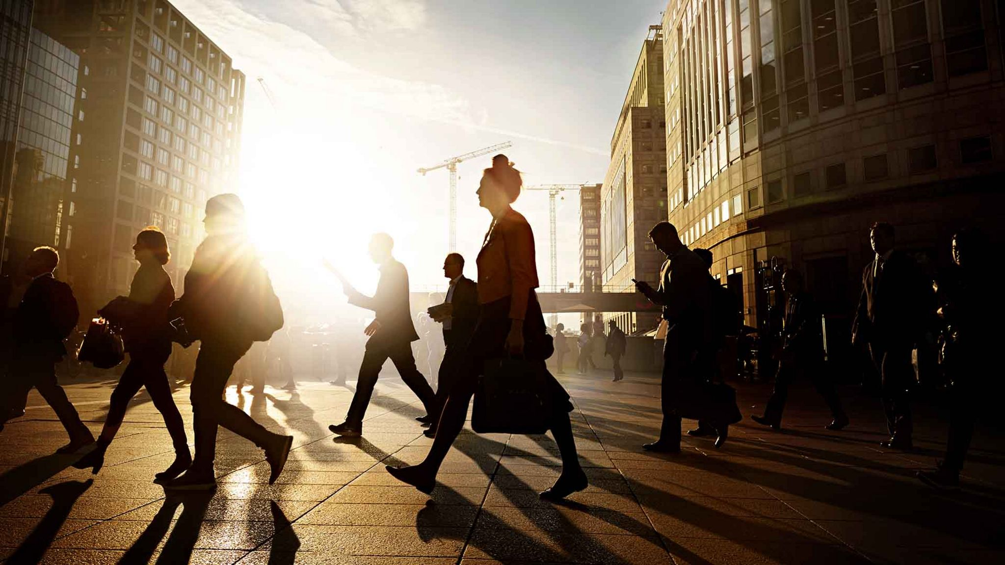 People in outline walking through city of London at sunrise