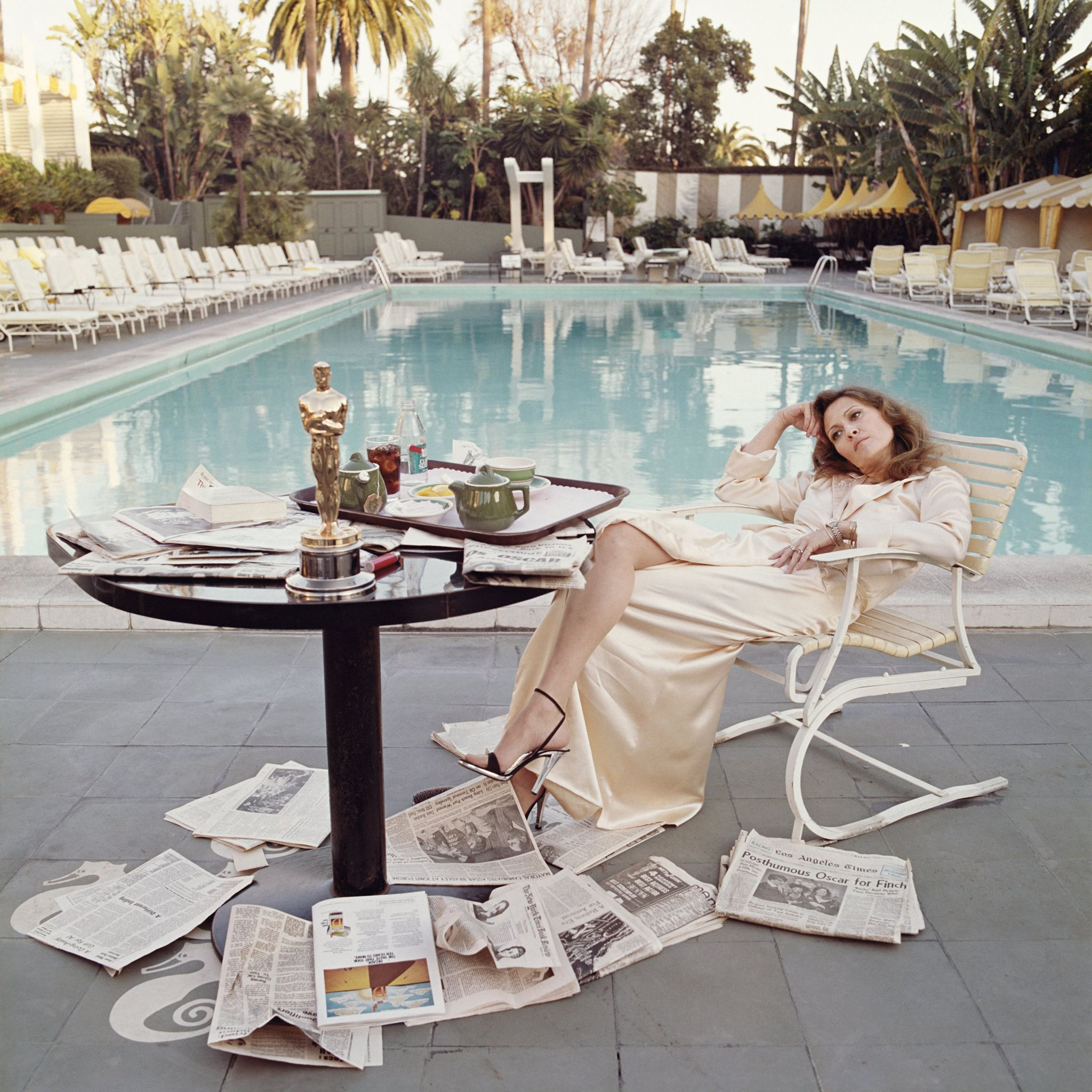 American actress Faye Dunaway by a pool with newspapers at the Beverley Hills Hotel in 1977