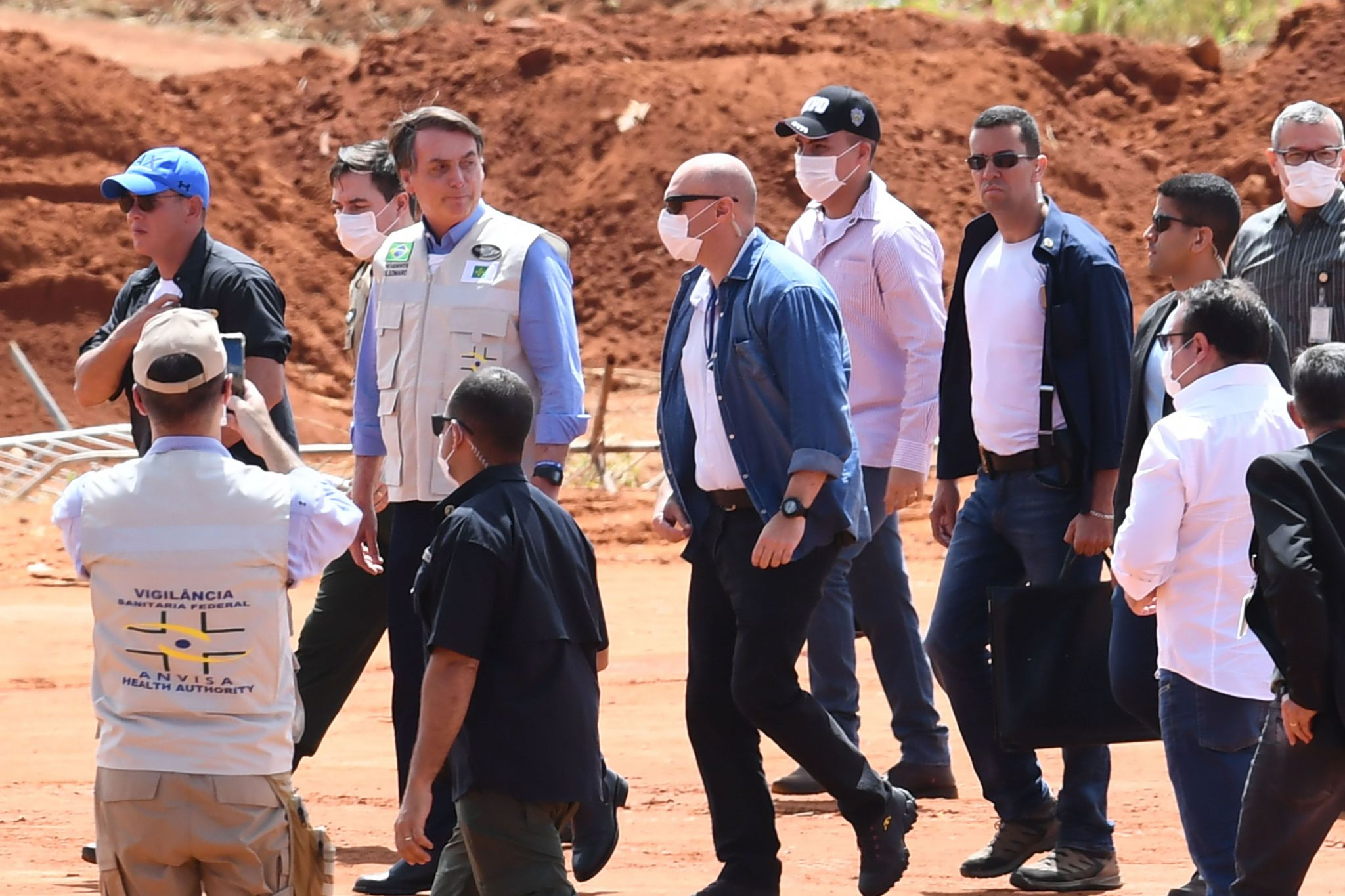 President Jair Bolsonaro (3-L) visits the construction site of a field hospital for people infected with the new coronavirus in Aguas Lindas, Goias State, Brazil on 11 April 2020.