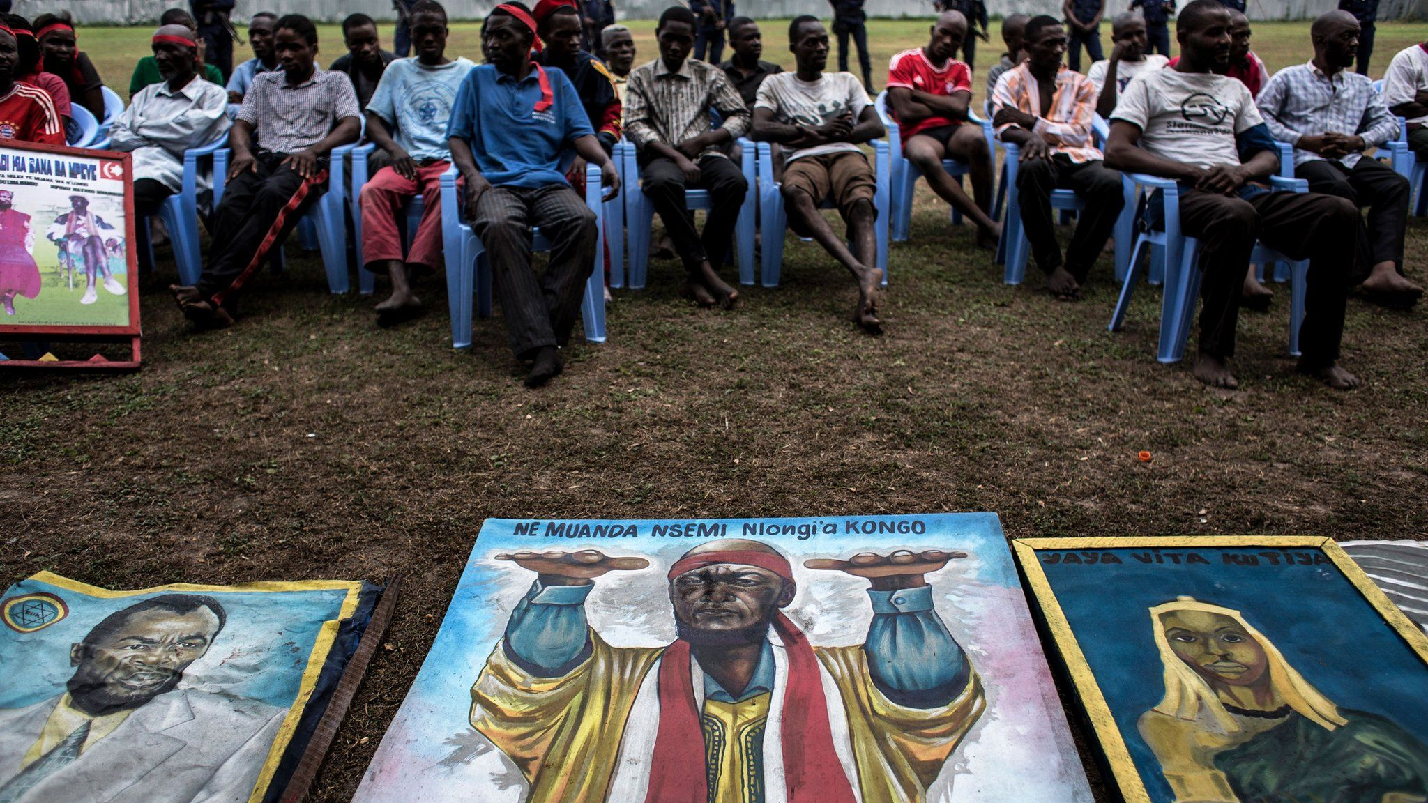 Men sit behind paintings of Bundu Dia Mayala group leader Muanda Nsemiare.