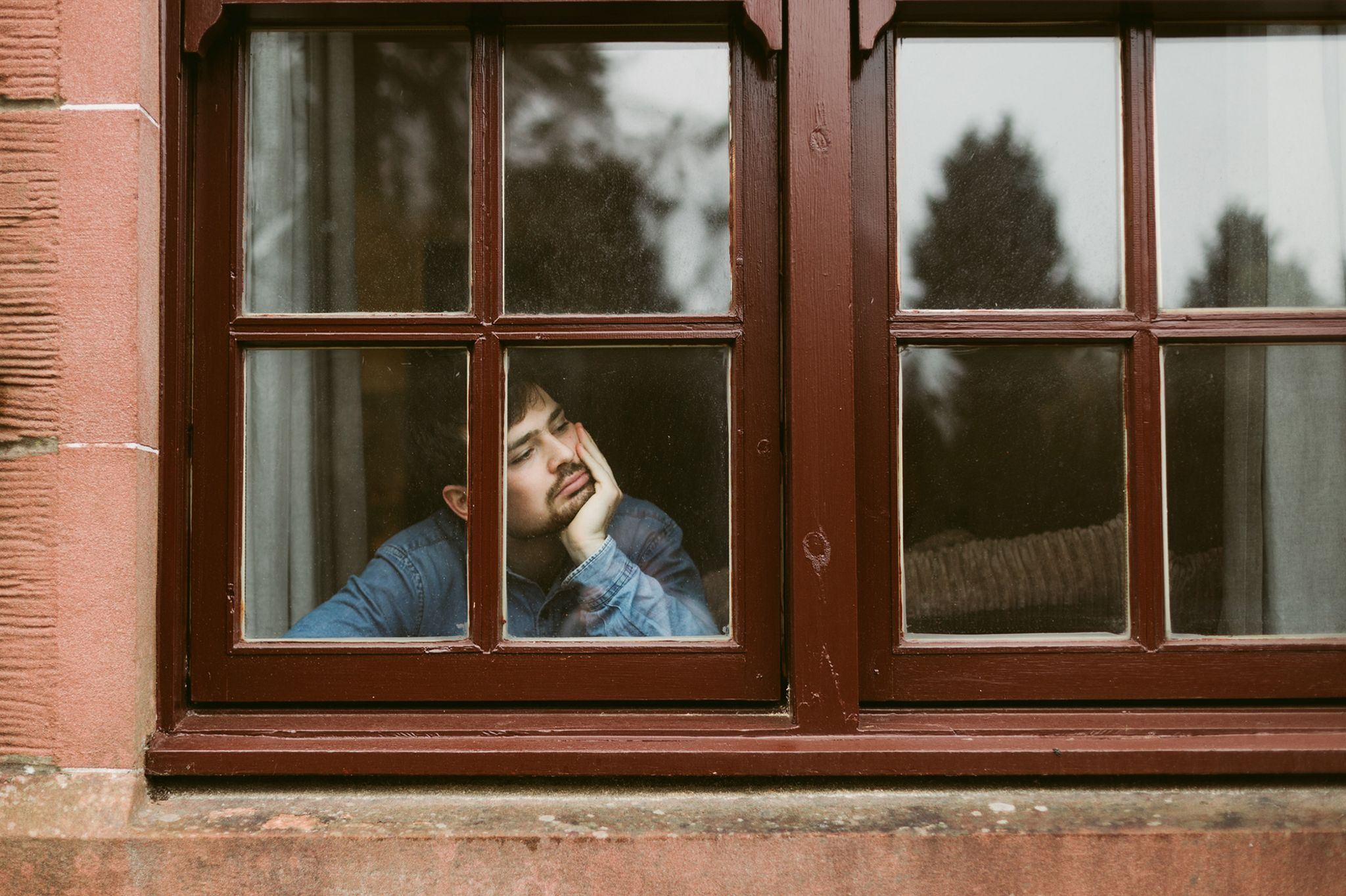 Bored man looking out of window