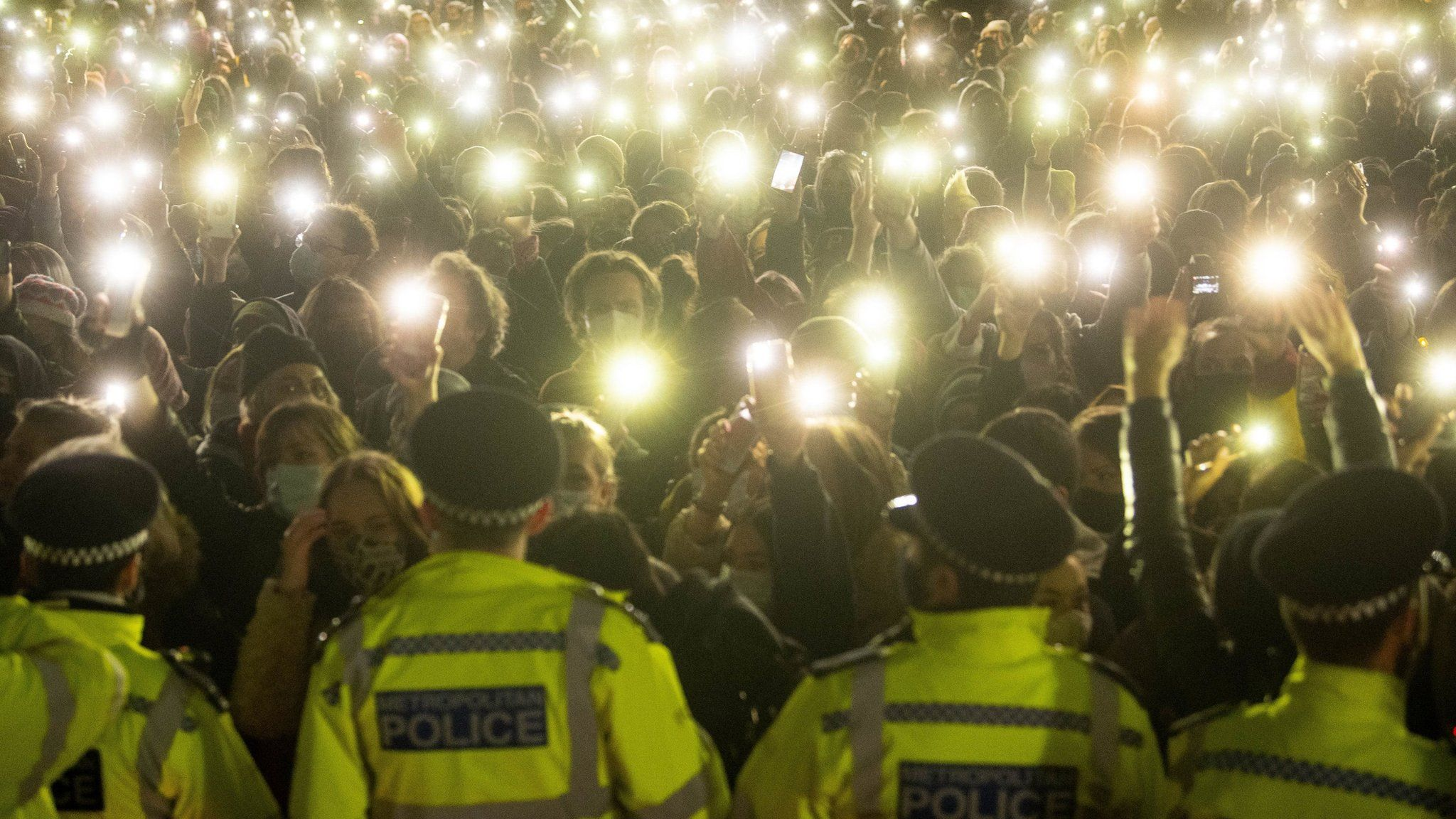 People at Saturday's vigil hold up torches and mobile phones in front of a line of uniformed police officers