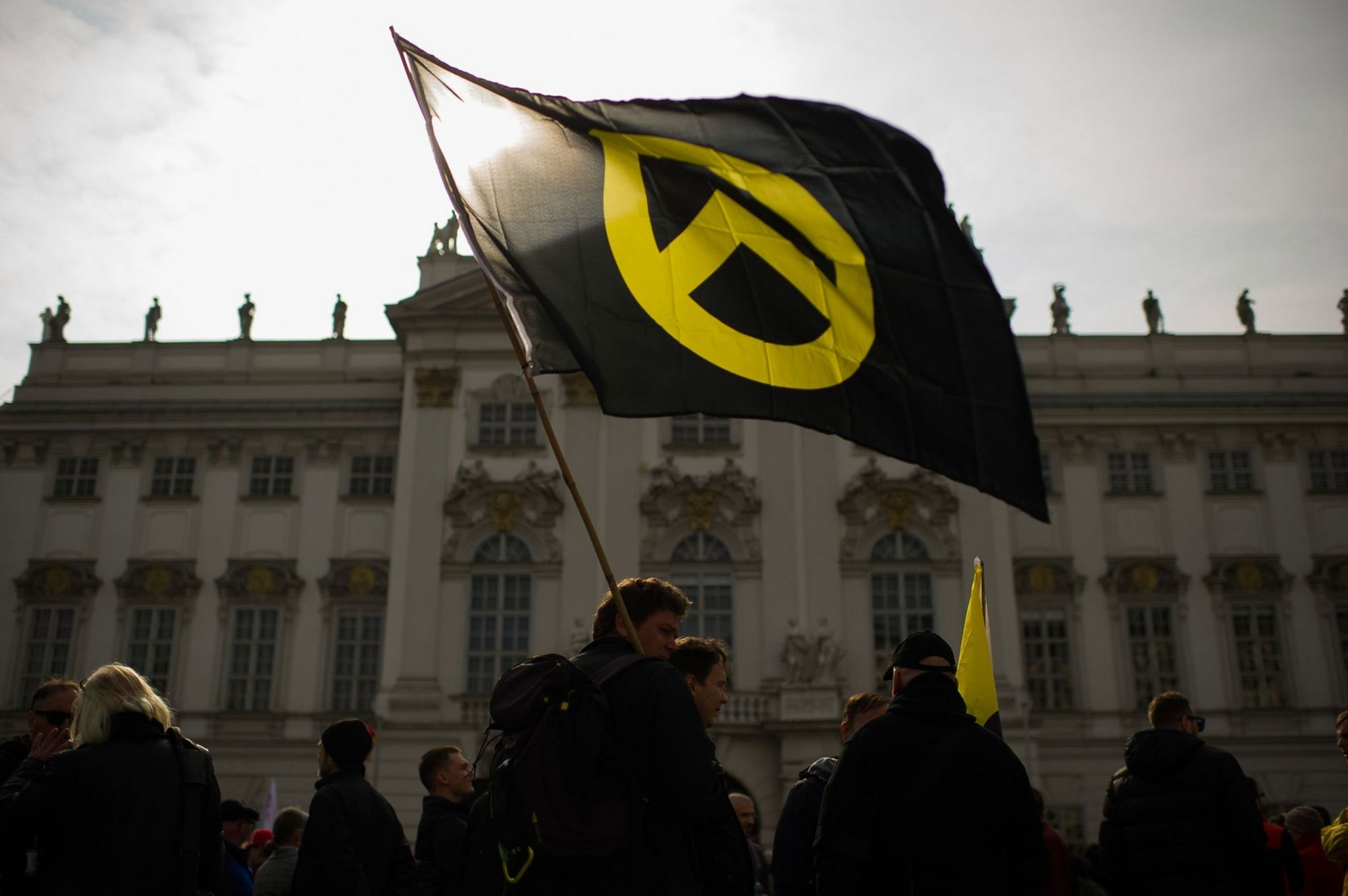 Protestor waves a flag with the logo of Generation Identity in front of the Justice Ministry. Vienna, April 2019