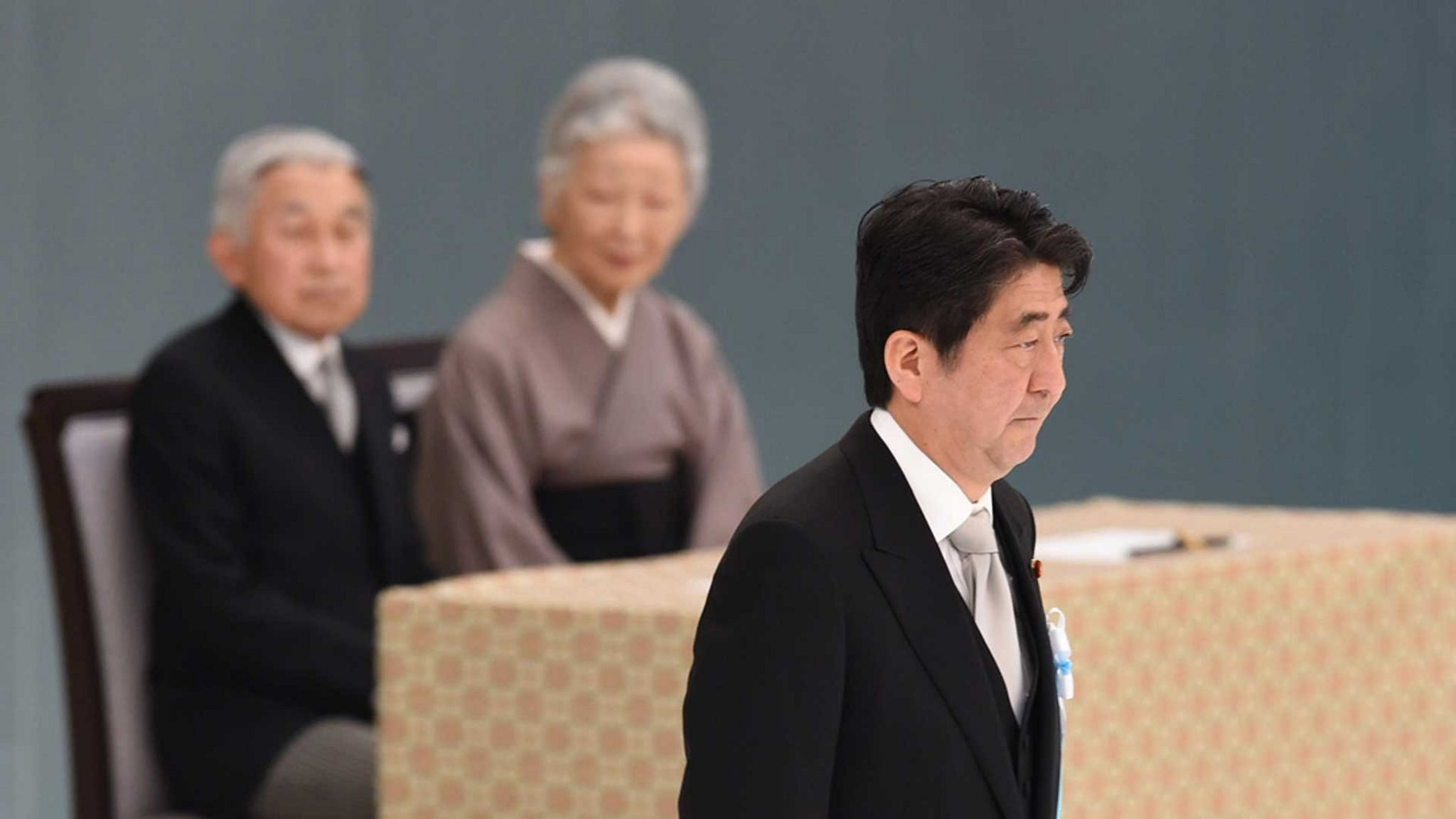 Japanese Prime Minister Shinzo Abe walks past Emperor Akihito and Empress Michiko during an annual memorial service for war victims, Tokyo, 2014