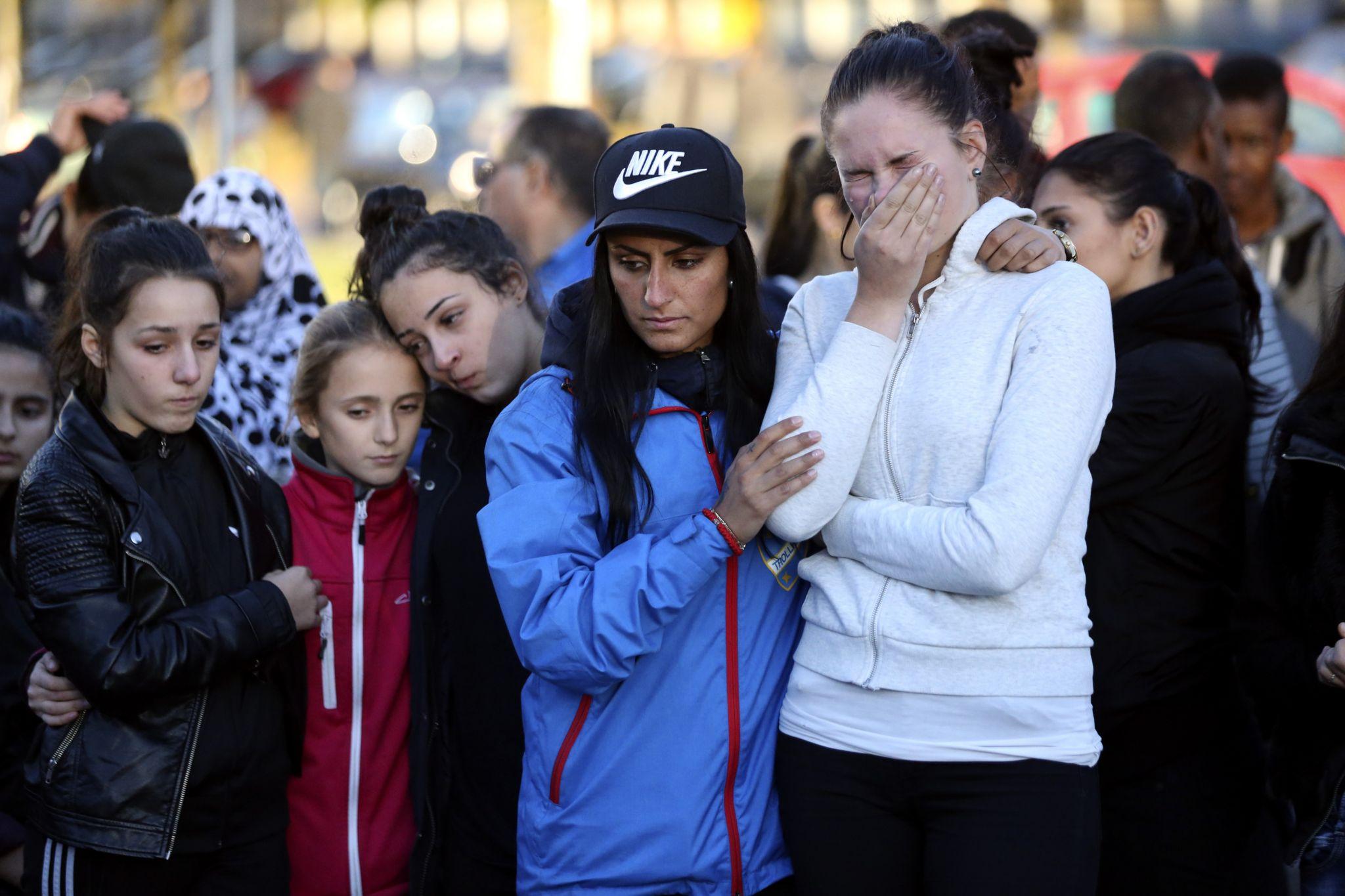 "People stand outside Kronan school after Thursday""s attack, in Trollhattan, Sweden"