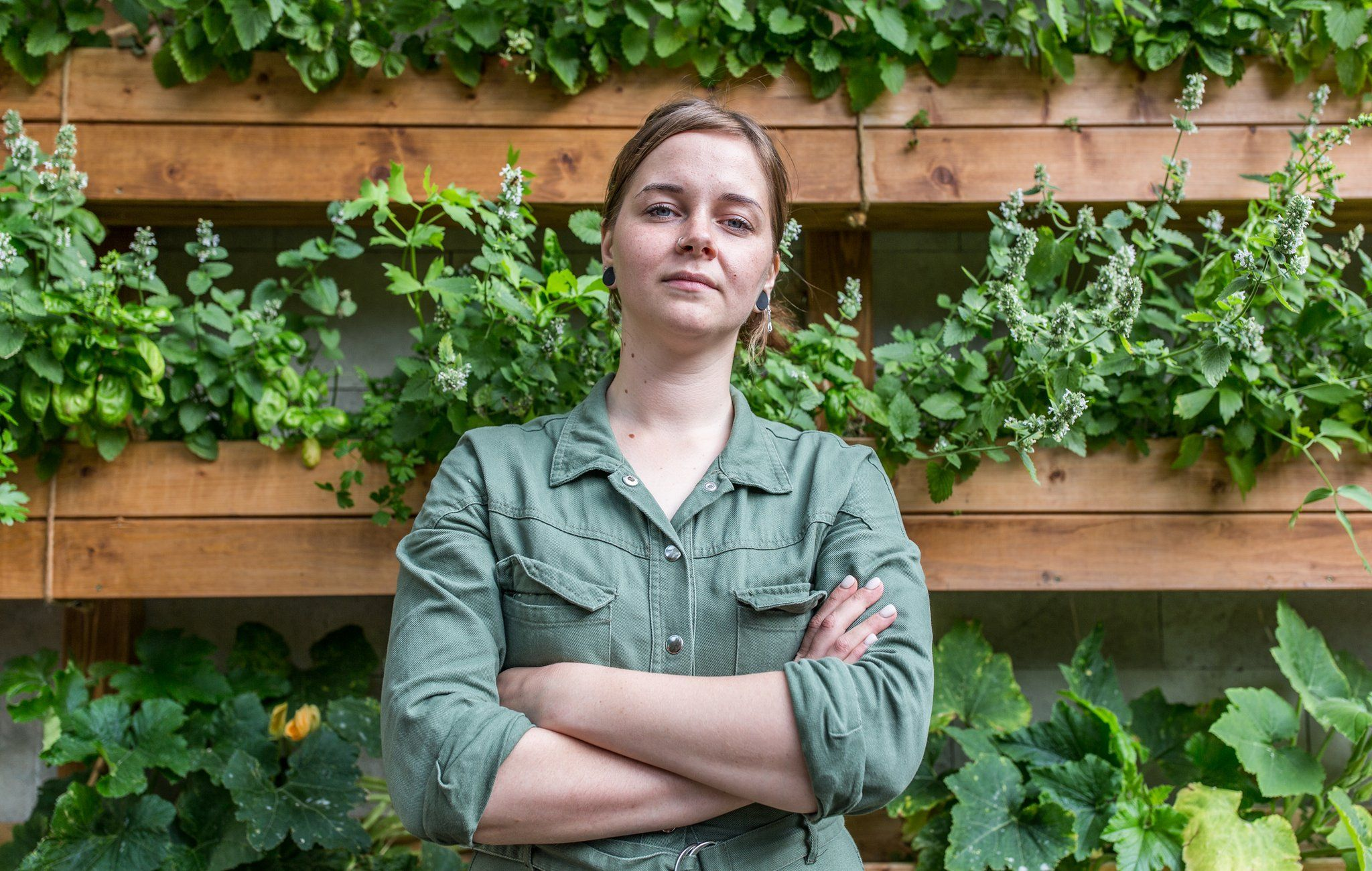 Viktoria Mosina, chef at Grun Cafe, standing in front of her allotment mounted on the wall of the restaurant