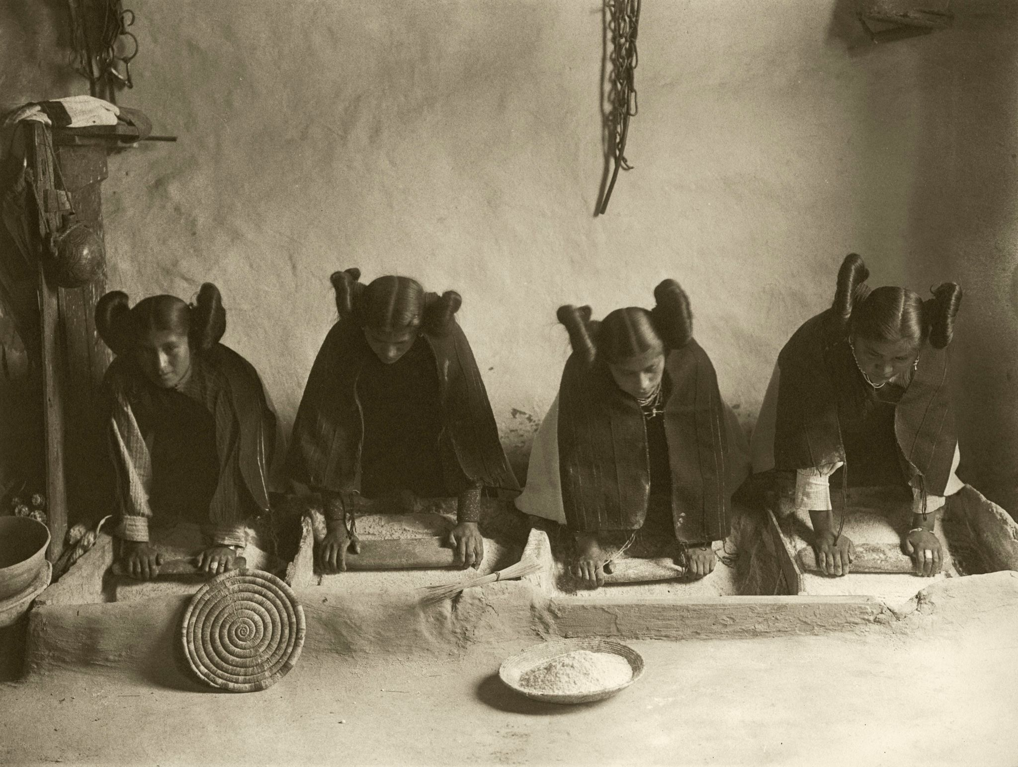 Hopi women grinding grain in a mealing trough.