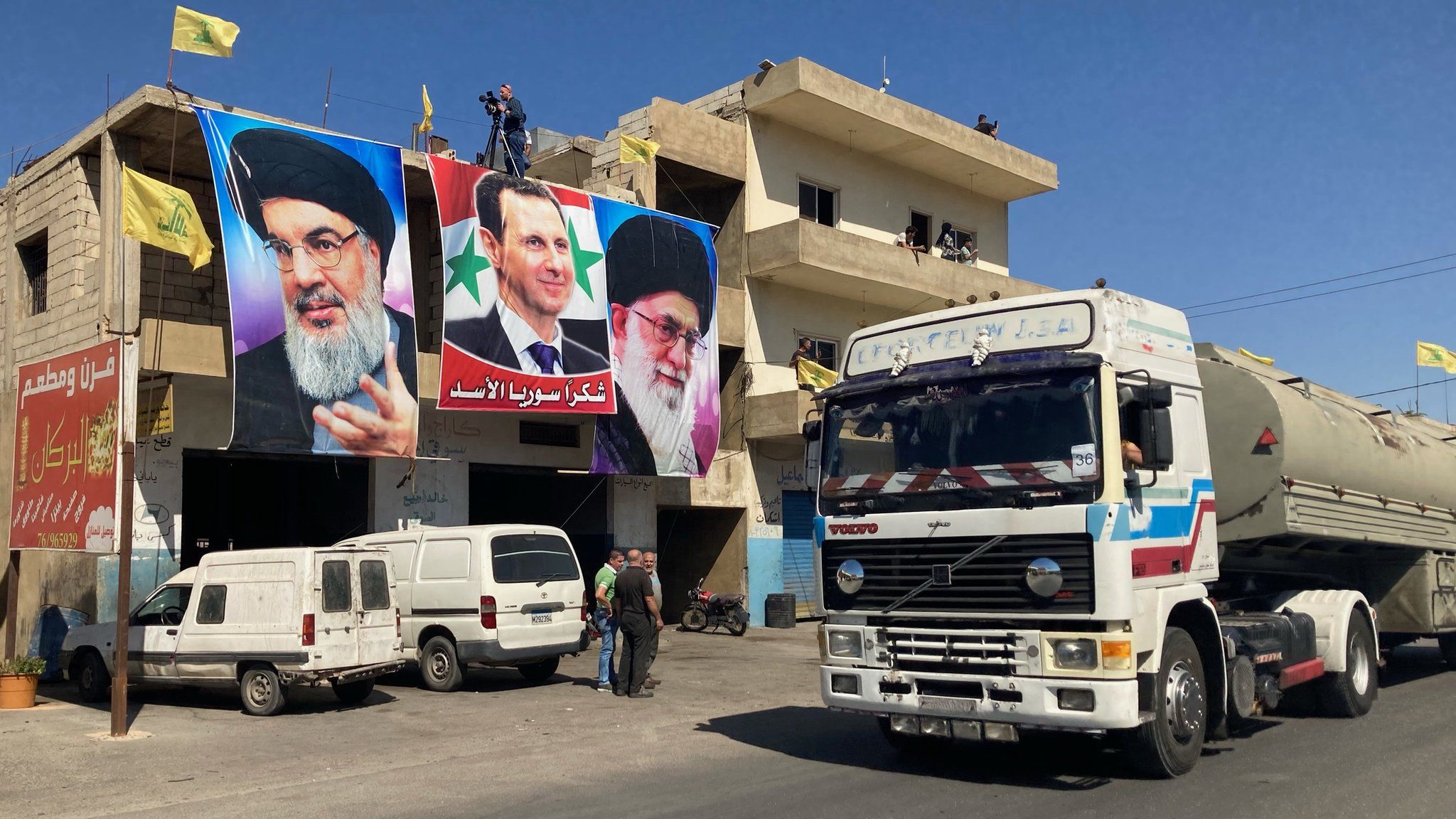 Posters of Hezbollah leader Hassan Nasrallah, Syrian President Bashar al-Assad and Iranian Supreme Leader Ali Khamenei on a building in al-Ain, as lorries bring Iranian fuel from Syria into Lebanon (16 September 2021)