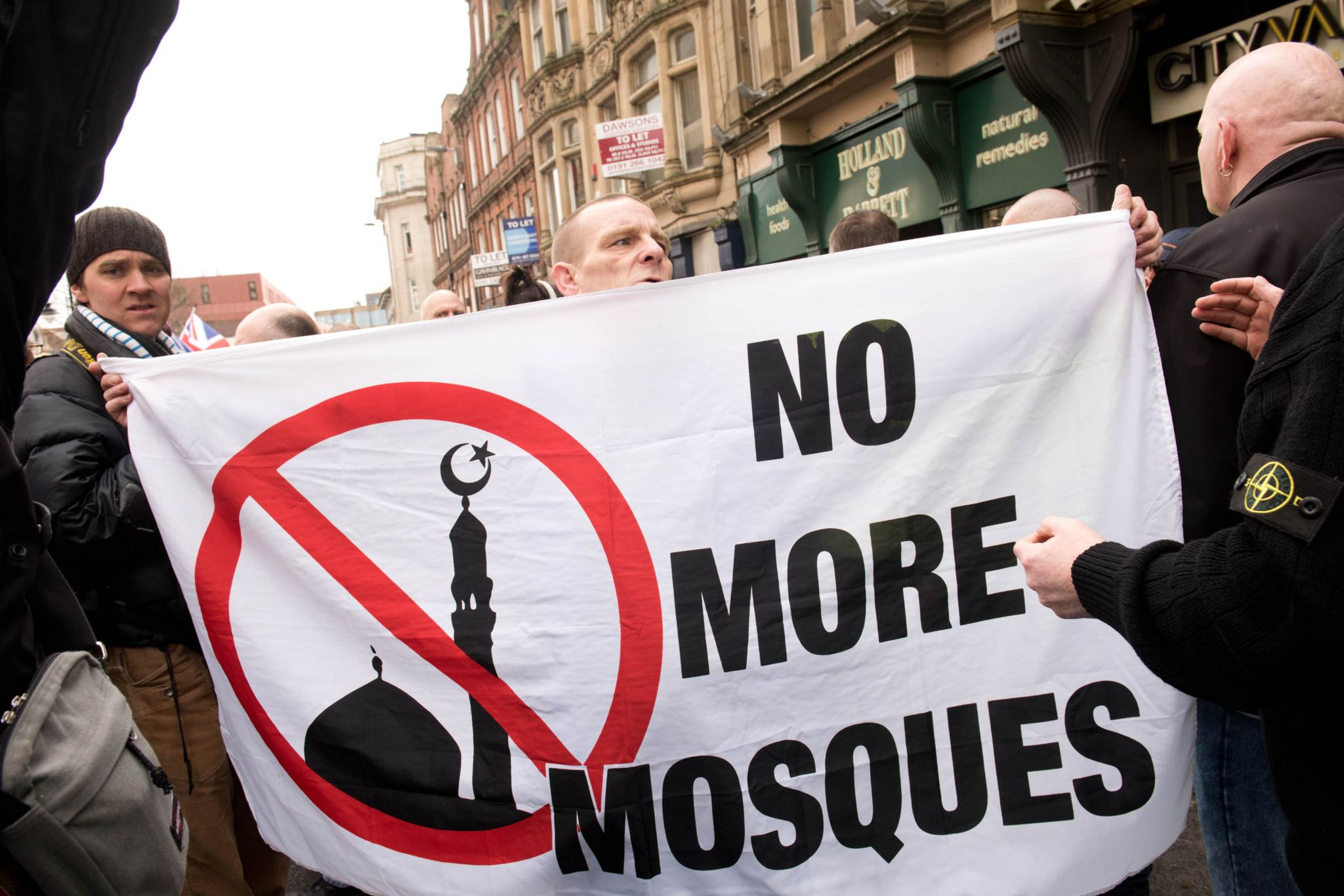 Protesters hold a banner reading No More Mosques during a demonstration by the UK branch of the German group Pegida in Newcastle upon Tyne in 2015
