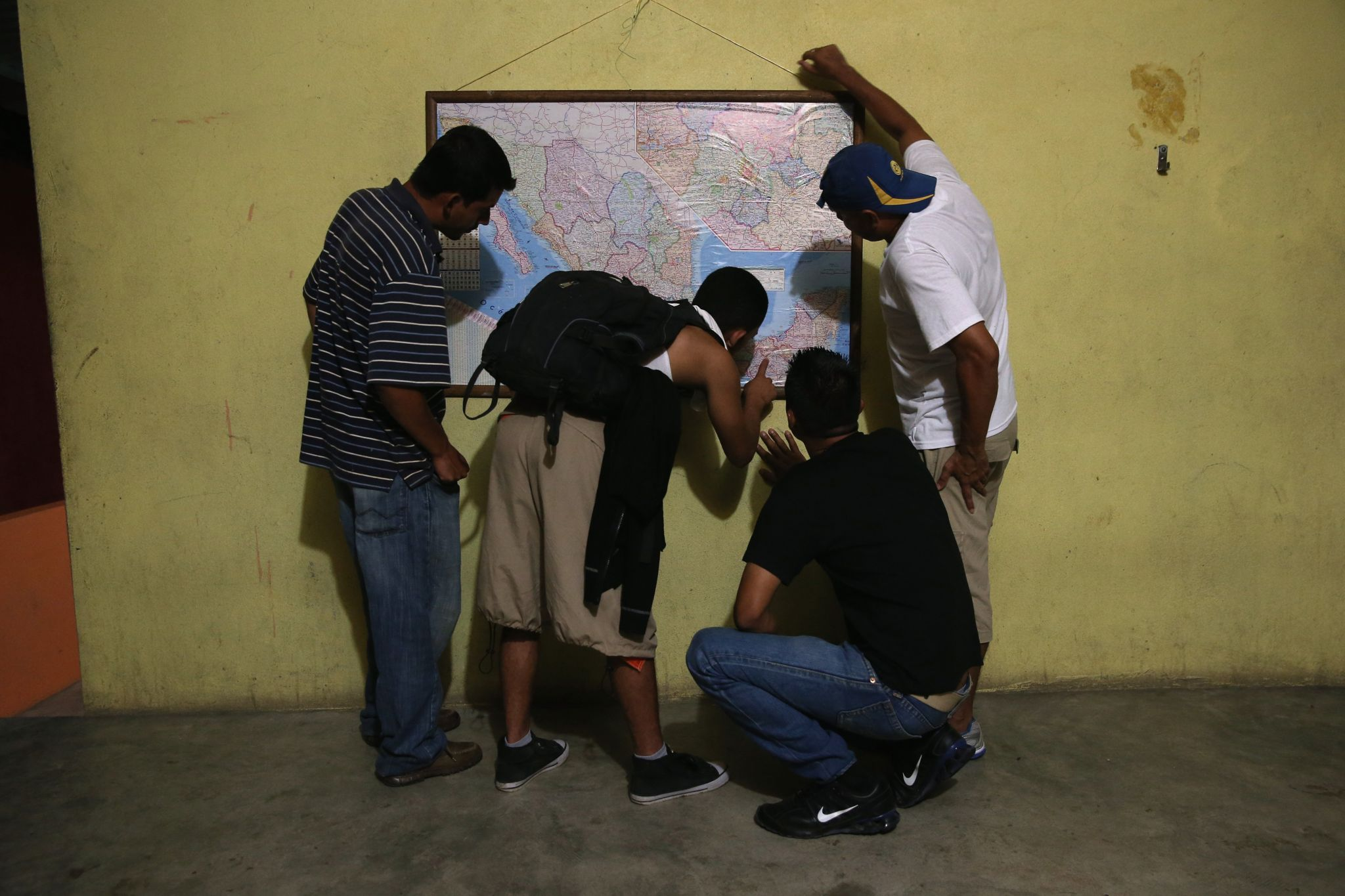 Honduran immigrants inspect a map of Mexico while staying at a shelter for undocumented immigrants on September 14, 2014 in Tenosique, Mexico.