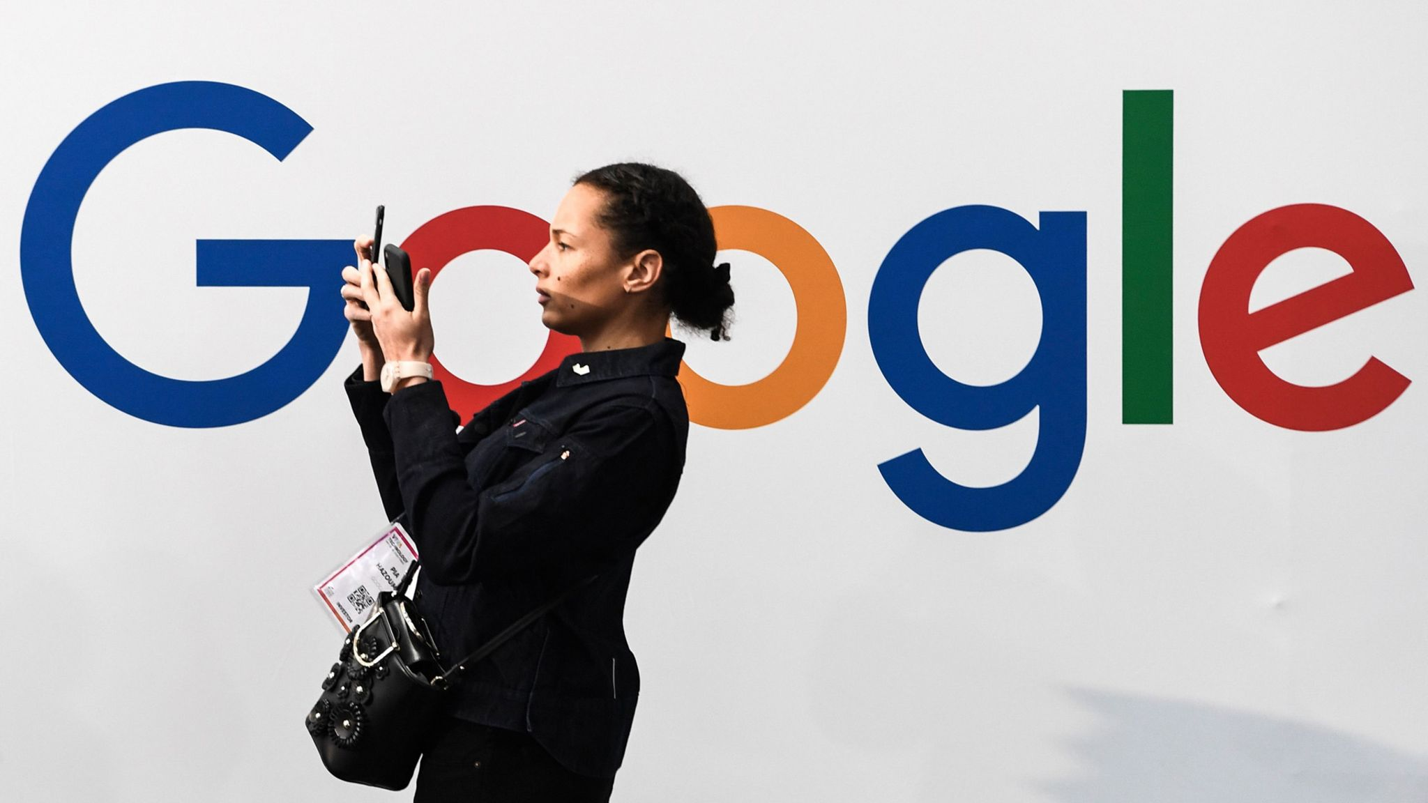 A woman takes a selfie by a Google sign
