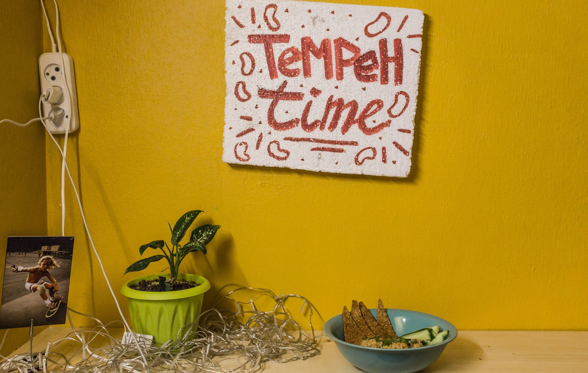 Polystyrene sign with 'Tempeh Time' painted on it in red above a bowl of food, on a bright yellow wall