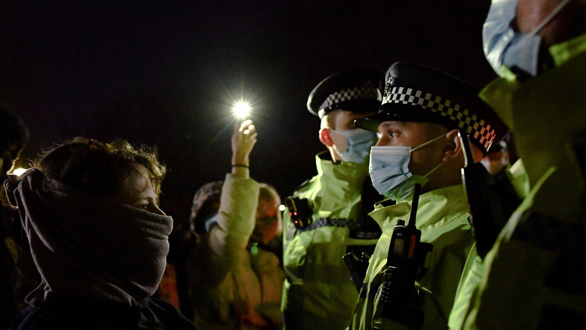 Mourners face police officers at a memorial site at the Clapham Common Bandstand