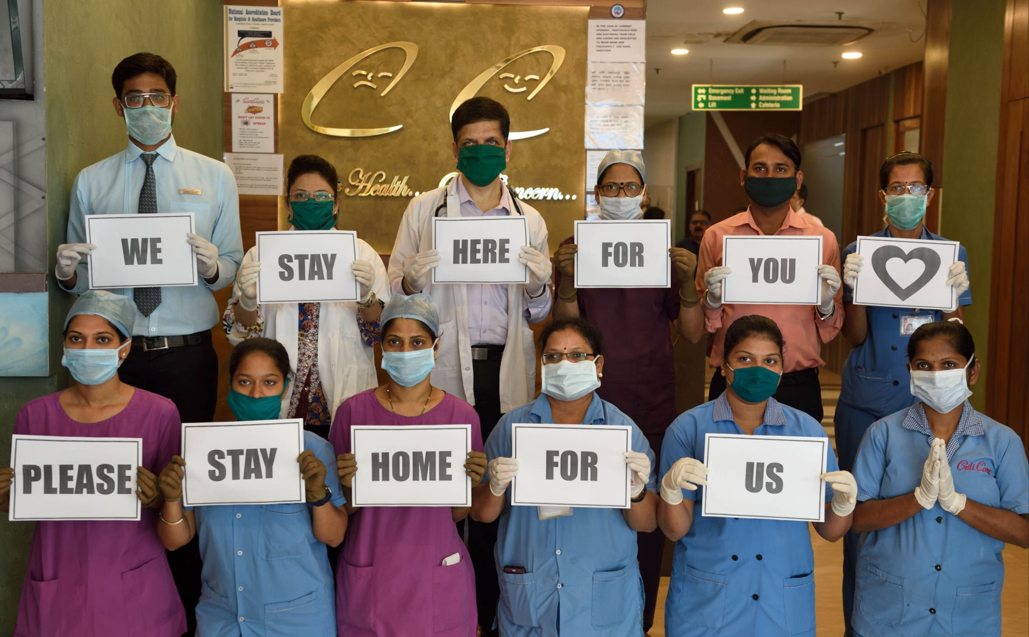 Indian hospital workers hold signs that say: 'we stay here for you please stay home for us'