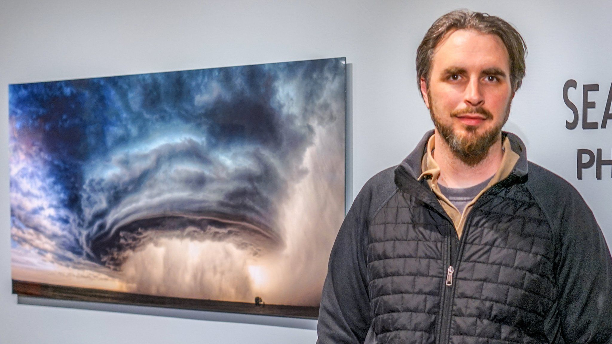 """Sean Heavey stands in front of his picture, """"The Mothership"""""""