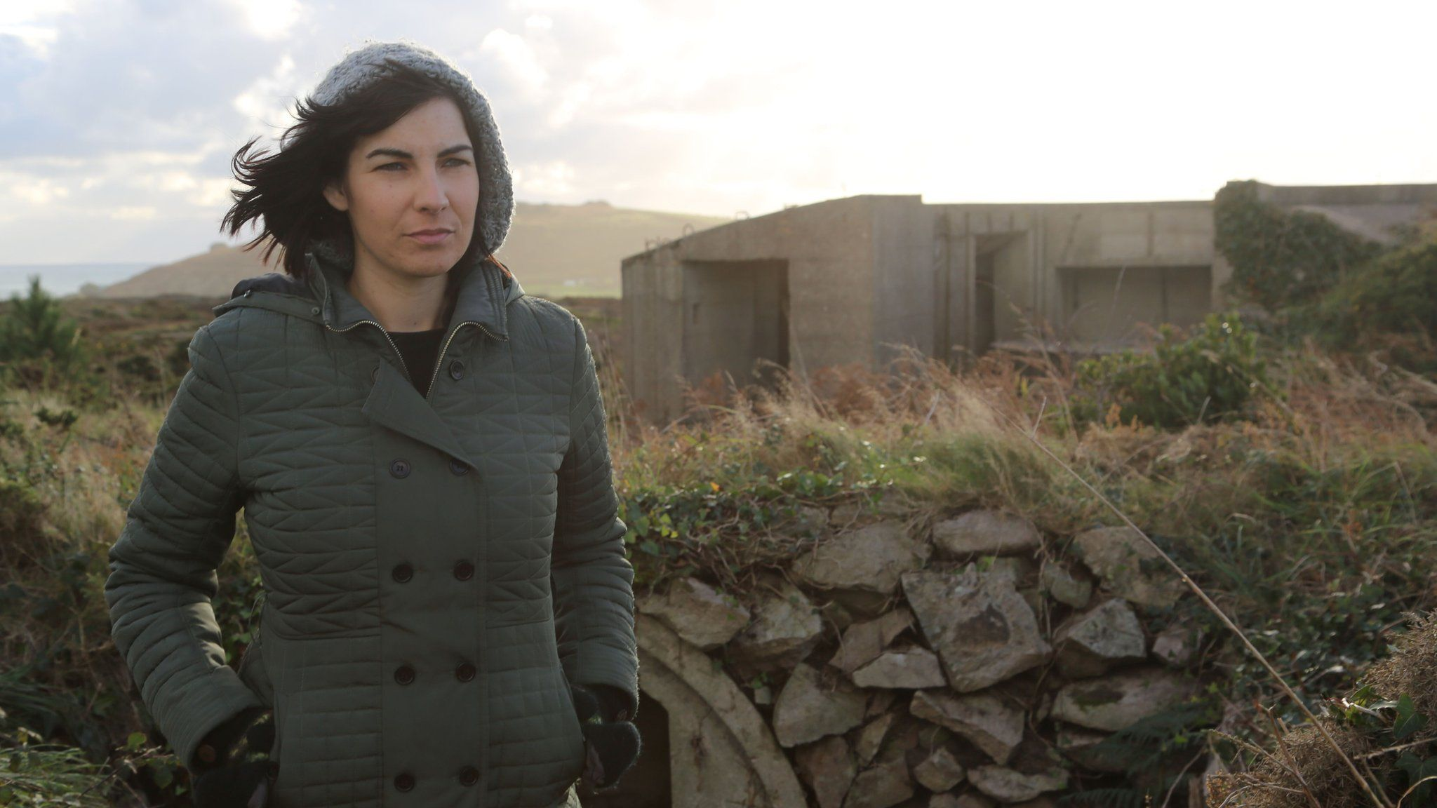 Woman standing next to World War Two fortifications