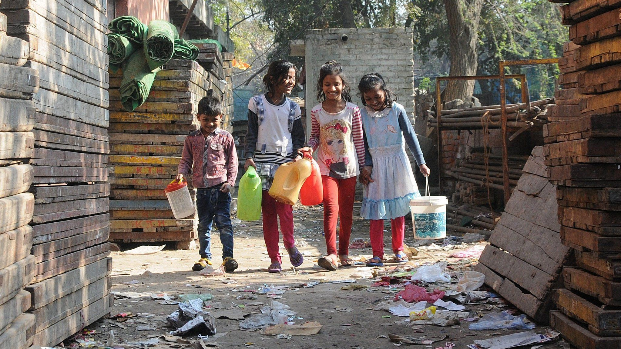 Indian children walk with containers to collect water from the hand pump, a ground water source of water , at the Azadpur area of in north Delhi, India (22 February 2016)