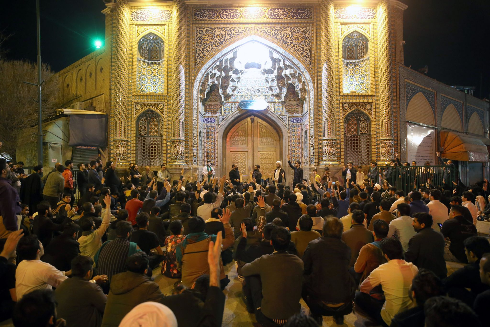 People gather outside the closed doors of the Fatima shrine in Iran's holy city of Qom