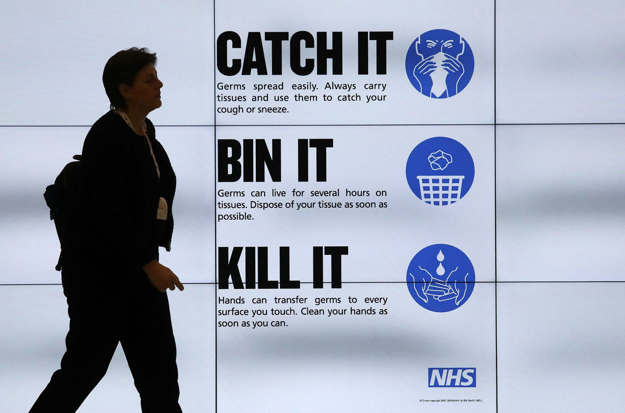 Woman walks past sign displaying public health advice