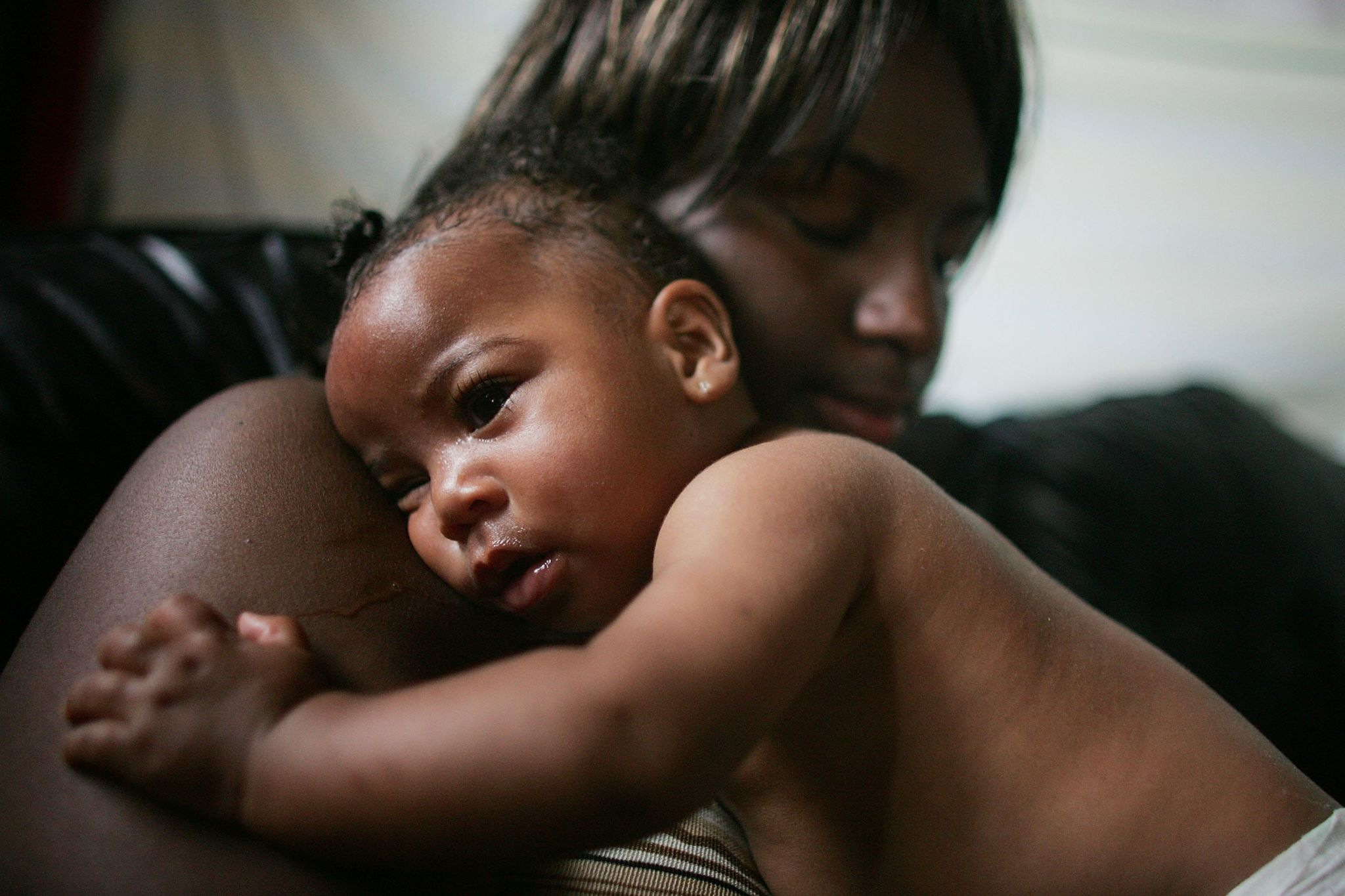 A woman, Shanika Reaux, holds her 6 month old baby Tatiana in their home