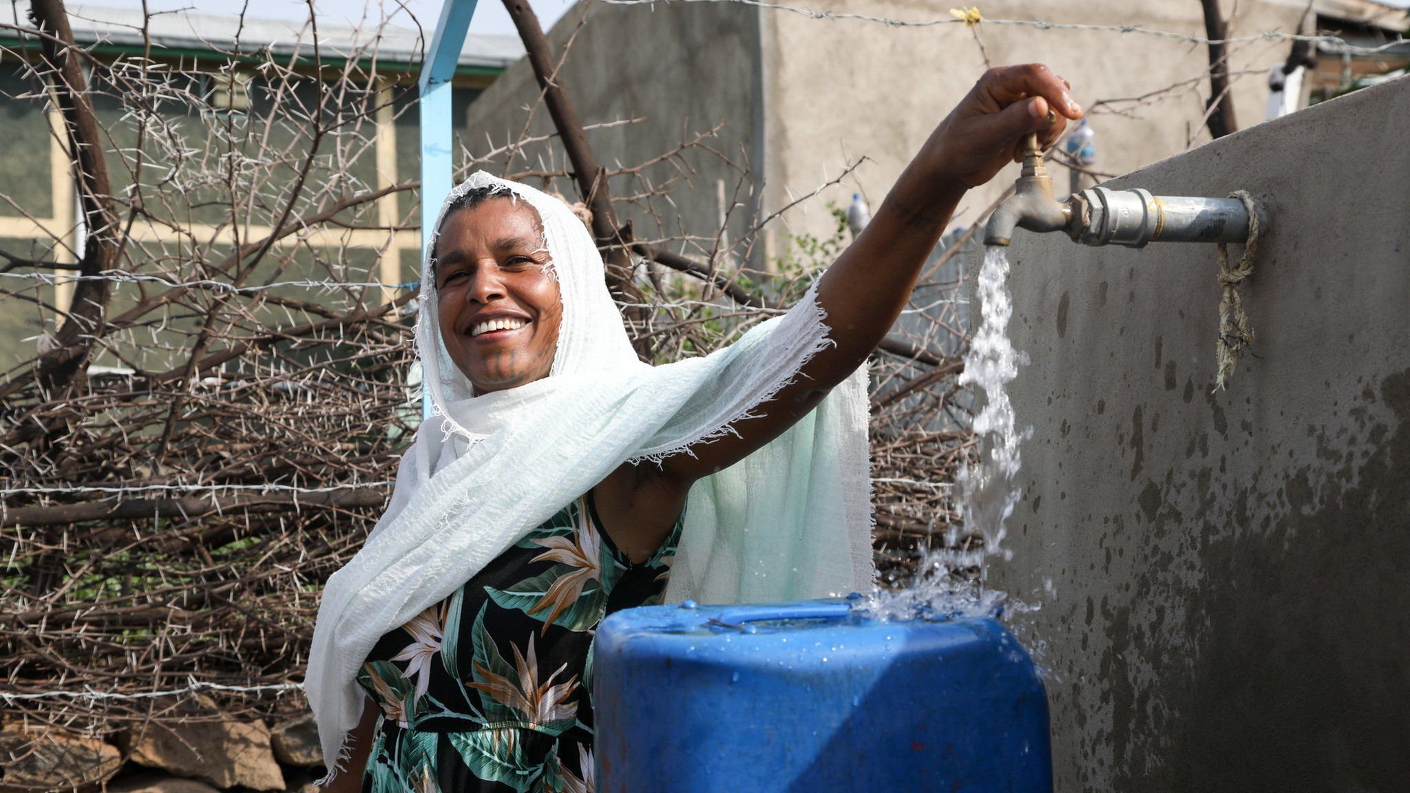 Wudenesh Negussie, 39, collects water from a local tap to take back to her family in Wolenchiti, Ethiopia, in 2019